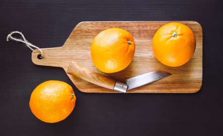 Oranges and old traditional pocket knife on a wooden cutting board