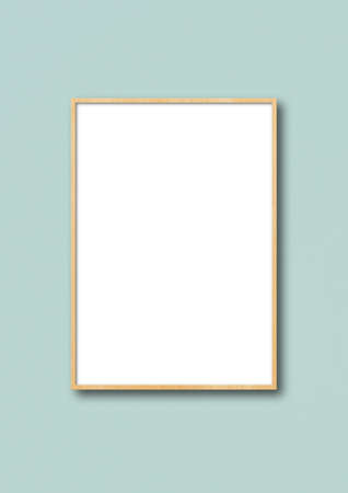 Wooden picture frame hanging on a light blue wall. Blank mockup template