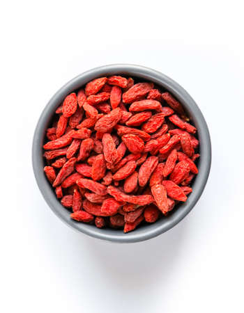 Goji berries dried fruit in a bowl isolated on white background. Top view Standard-Bild - 155804318