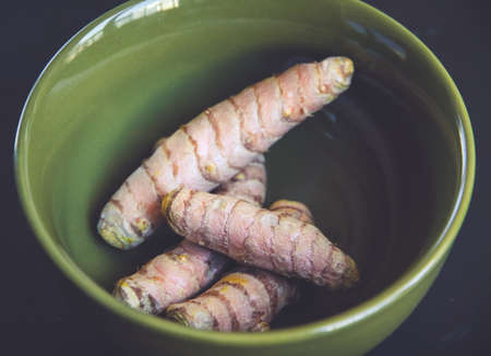 Turmeric root in a bowl. Top view