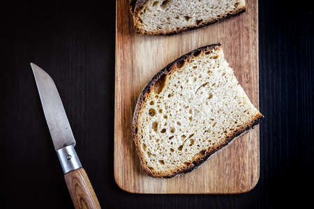 Traditional French country bread slices and pocket knife on a wooden cutting board. Top view
