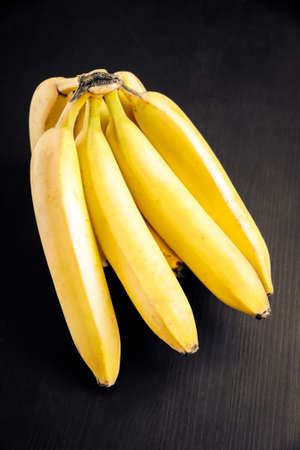 Bunch of organic bananas on a black wooden table
