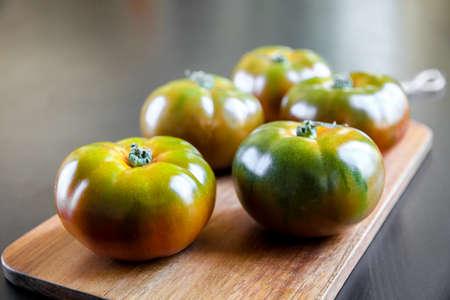Black Krim organic tomatoes on a wooden cutting board Standard-Bild