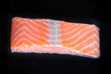 Salmon steak isolated on black background. Top view Standard-Bild