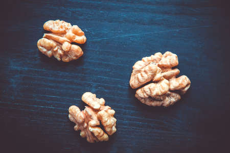 Walnut kernels on a black wooden table. Closeup view
