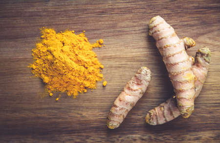 Turmeric root and spice powder on a wooden cutting board. Top view Standard-Bild
