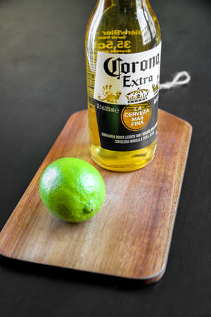 Paris/France - January 6, 2020 : Bottle of Corona Mexican beer and lime on a wooden cutting board Editorial