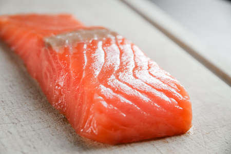 Salmon steak on a wooden cutting board. Close-up view