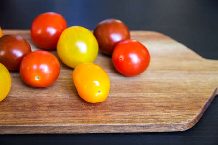 Colorful cocktail tomatoes on a wooden cutting board