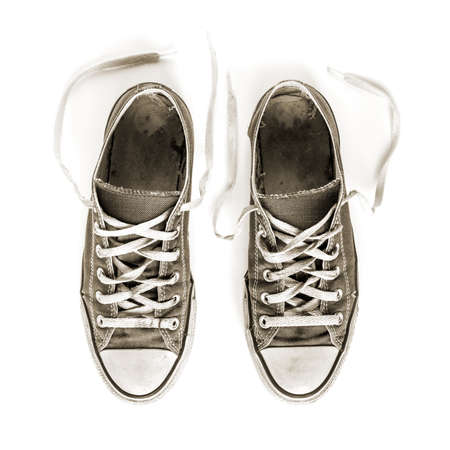 Old black generic sneakers isolated on white background