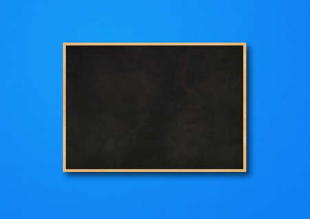 Traditional black board isolated on a blue background. Blank horizontal mockup template Standard-Bild