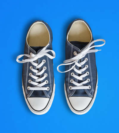 Blue generic sneakers isolated on cyan background Standard-Bild