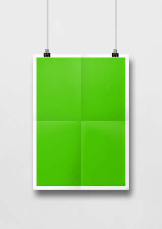 Green folded poster hanging on a white wall with clips. Blank mockup template Standard-Bild