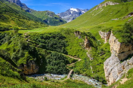 Mountain river and wood bridge in Vanoise national Park alpine valley, Savoie, French alps Archivio Fotografico