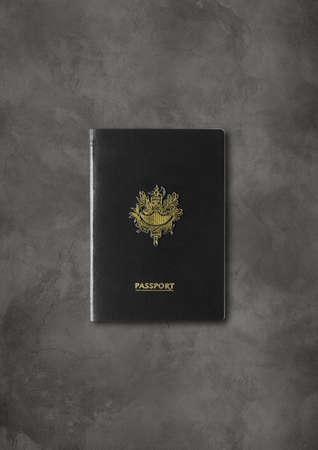 Generic black passport isolated on dark concrete background