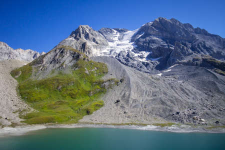 Long lake and Grande Casse Alpine glacier landscape in French alps