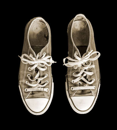 Old generic sneakers isolated on black background