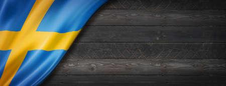 Sweden flag on black wood wall. Horizontal panoramic banner. Archivio Fotografico