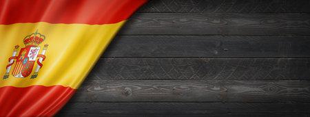 Spain flag on black wood wall. Horizontal panoramic banner. Archivio Fotografico