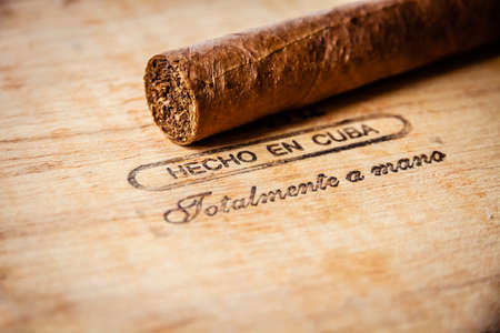 Brown cuban cigar on vintage wooden box with inscription in spanish : made by hand in Cuba