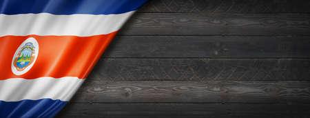 Costa Rica flag on black wood wall. Horizontal panoramic banner. Archivio Fotografico