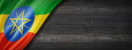 Ethiopia flag on black wood wall. Horizontal panoramic banner. Archivio Fotografico