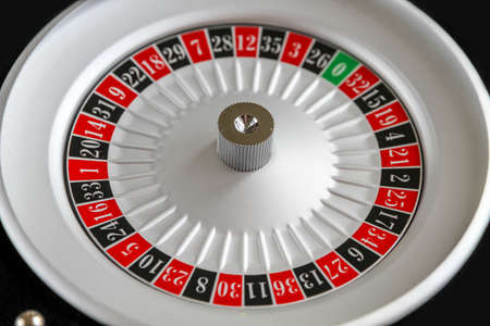 Casino roulette wheel close up view. Black background