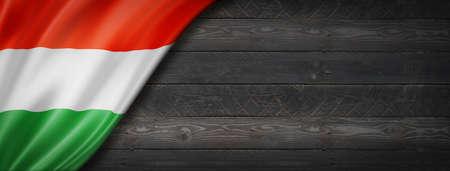 Hungary flag on black wood wall. Horizontal panoramic banner.