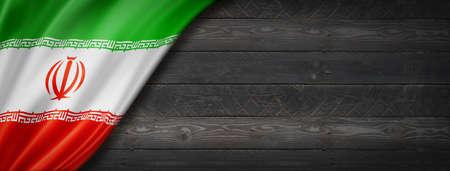 Iran flag on black wood wall. Horizontal panoramic banner.