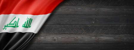 Iraq flag on black wood wall. Horizontal panoramic banner.