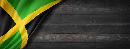 Jamaica flag on black wood wall. Horizontal panoramic banner.