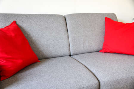 Grey sofa close-up view with red cushions