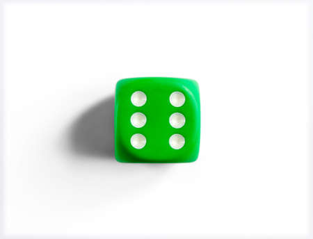 Number 6 on green dice. White background. Top view