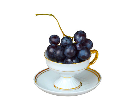 Blue grapes in a cup isolated on white background