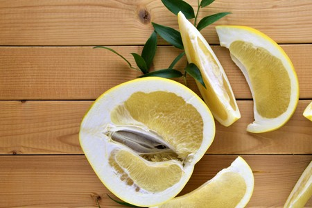 A half of yellow fresh pomelo and it's pieces on simple wooden background with green decorative leafs, close up of fruit