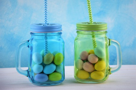 Sky-blue and green transparent glass jars with colored Easter eggs
