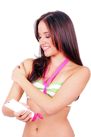 Woman applying suntan lotion in a white background