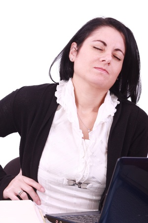 Young woman sitting at her laptop with a lot of work in front of her. She has a pain in her neck  back photo
