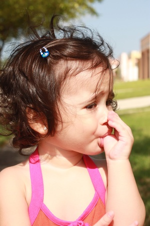 Little baby girl, sucking her thumb walking in the park photo