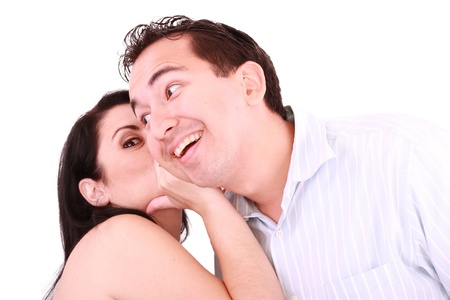 bruit: pretty girl talking secret to young man in his ear, man smiling over isolated white background