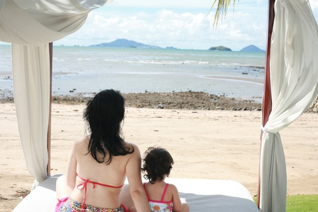 young lovely mother and her little daughter on tropical white bed close to the beach in the glow of the evening sun photo