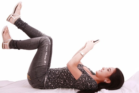beautiful young girl laying on a pillow chatting on a cell phone  photo