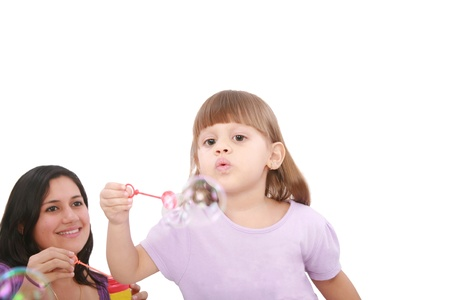 Portrait of funny lovely little girl blowing soap bubbles with her mom. Little girl on focus. photo