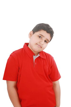 Portrait of a happy little young boy standing with hands in pocket over white background  photo
