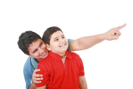 padre e hijo: Retrato de un padre joven feliz que muestra algo intersting a su hijo contra el fondo blanco