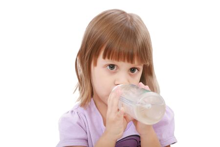 Little girl drinking water of her bottle. White background  photo