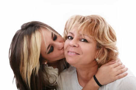 Closeup of young girl kissing her mom isolated on a white background photo