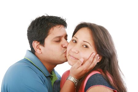 Portrait of woman looking at camera with man near by kissing her  photo