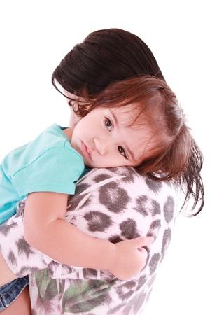 niños tristes: Niña abrazando a su madre. Aislado en blanco. Foto de archivo