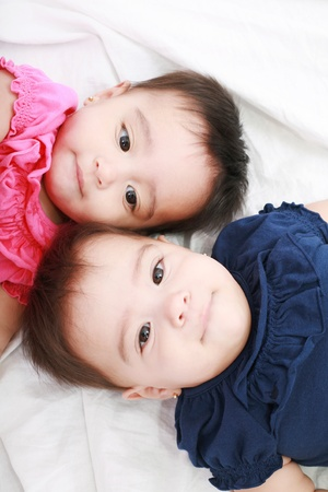 Twin baby sisters lay down in the bed